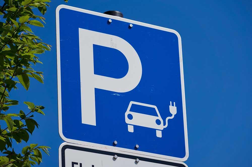 Parkplatzschild mit Möglichkeit, Elektroautos zu laden